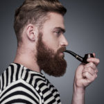 Side view of confident young bearded man in striped clothing smoking a pipe and looking away while standing against grey background